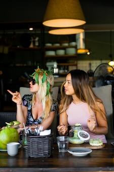 Deux belles amies prenant son petit déjeuner ensemble dans un café.