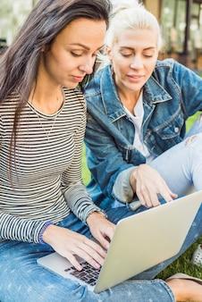Deux belles amies travaillant sur un ordinateur portable