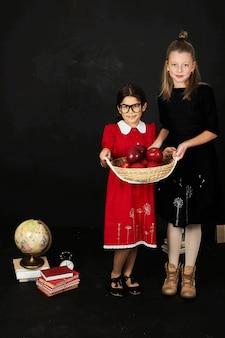 Deux belles copines écolières avec des livres et un panier de pommes sur un fond noir