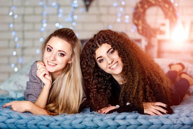 Deux belles copines heureuse dans des vêtements décontractés, allongée sur un canapé dans un salon