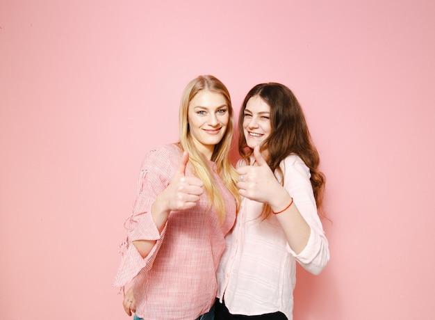 Deux belles copines s'amusant sur fond rose.