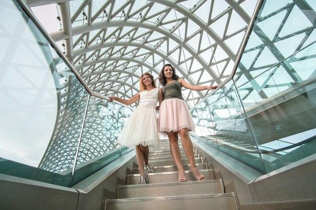 Deux belles copines sont photographiées, font du selfie, sur un smartphone sur le pont de la paix à tbilissi, en géorgie.