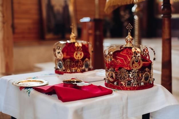 Deux belles couronnes avec de l'or et du tissu rouge se tiennent sur une table dans l'église avant le baptême du bébé