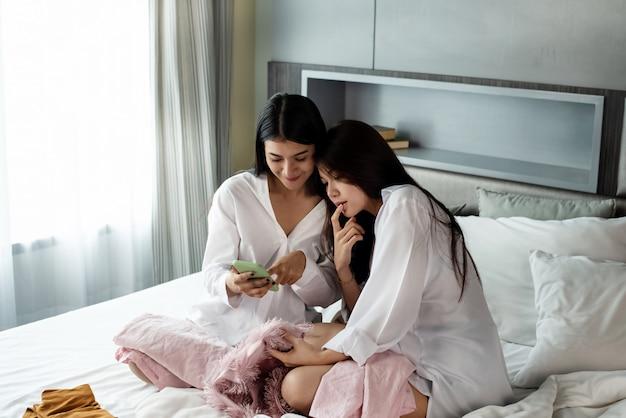 Deux belles dames assises sur le lit, beaucoup de tissu de mode autour, utilisant un téléphone portable pour faire du shopping en ligne, avec un sentiment de bonheur, faisant de l'activité ensemble