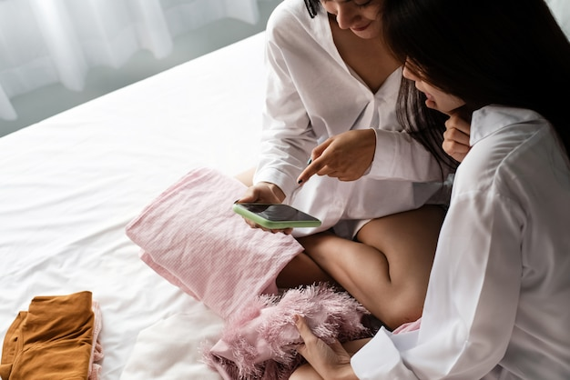 Deux belles dames utilisant un téléphone portable pour faire du shopping en ligne, avec un sentiment heureux, une bonne amitié de couple amoureux