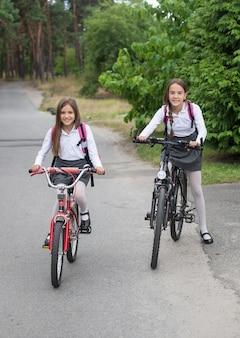 Deux belles écolières allant à l'école à vélo