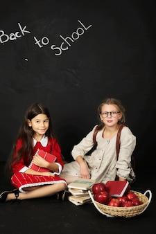 Deux belles écolières copines assis avec des livres et un panier de pommes sur un fond noir