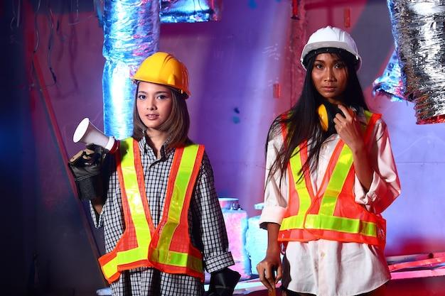 Deux belles femmes asiatiques ingénieur architecte dans un casque jaune, sécurité vaste, méga téléphone, concept femme peut faire la destruction zone de chantier de construction salle de transpalette à main mode fond bleu rouge