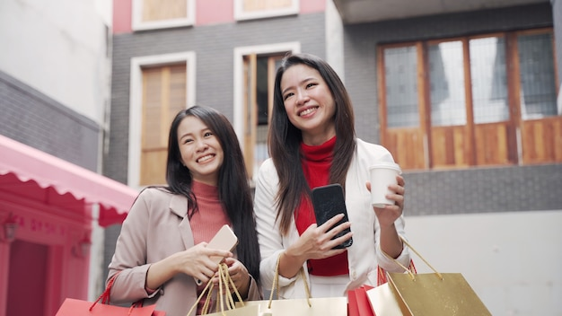 Deux belles femmes asiatiques avec des sacs à provisions dans la ville