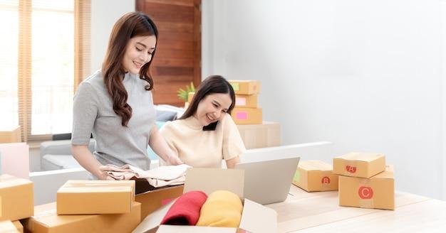 Deux belles femmes asiatiques vérifient les commandes sur des ordinateurs portables via internet.