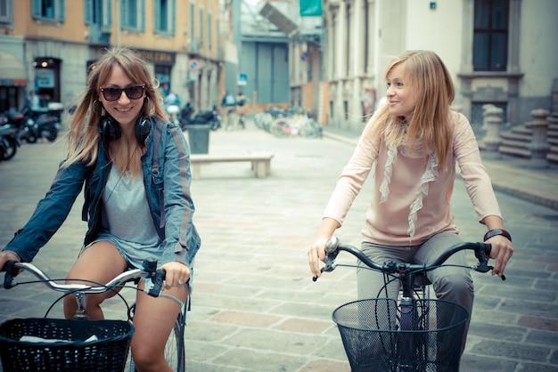 Deux Belles Femmes Blondes, Faire Du Shopping à Vélo Photo Premium