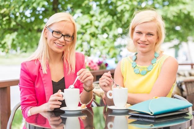 Deux belles femmes buvant du café au bar