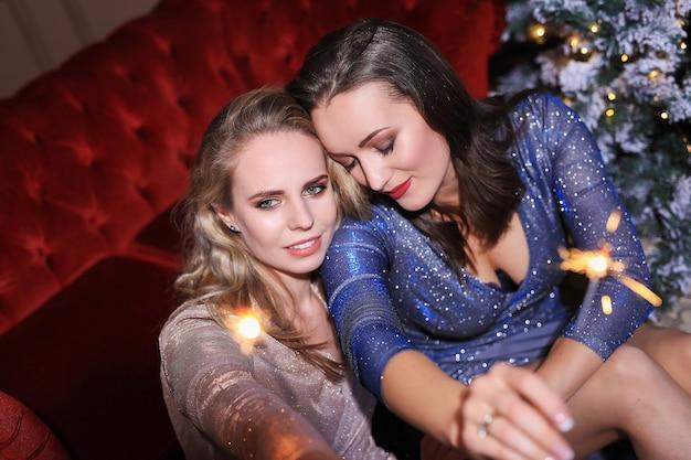 Deux belles femmes célébrant noël avec une robe de mode. noël à la maison