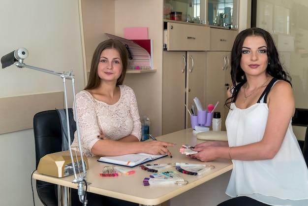 Deux belles femmes dans un salon de beauté avec une palette d'ongles