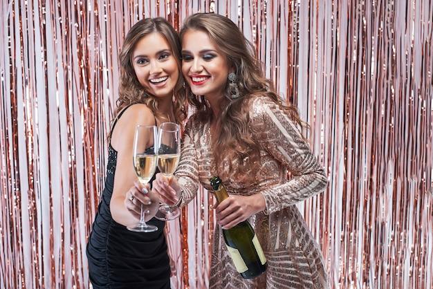 Deux belles femmes élégantes tinter les verres de champagne.