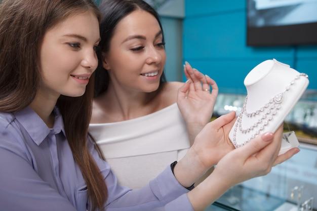 Deux belles femmes examinant un collier de diamants en vente au magasin de bijoux