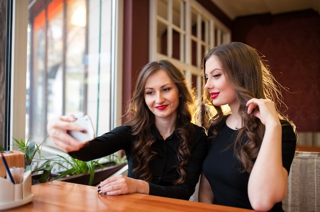 Deux belles femmes font selfi et boivent du café