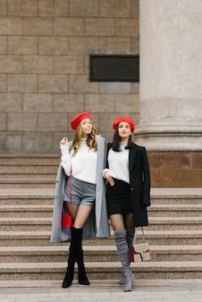 Deux belles femmes françaises en bérets, regardant la caméra et souriant tout en marchant ensemble en plein air près des marches d'un immeuble classique.