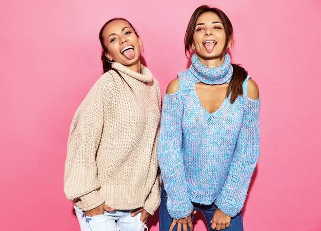 Deux belles femmes magnifiques souriantes sexy. femmes chaudes debout dans des chandails élégants blancs et bleus, sur un mur rose. montrant leur langue