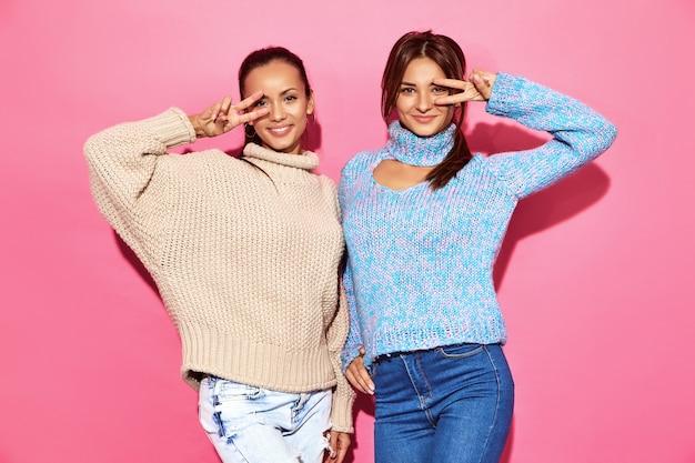 Deux belles femmes magnifiques souriantes sexy. femmes chaudes debout dans des chandails élégants blancs et bleus, sur un mur rose. montrant le signe de la paix