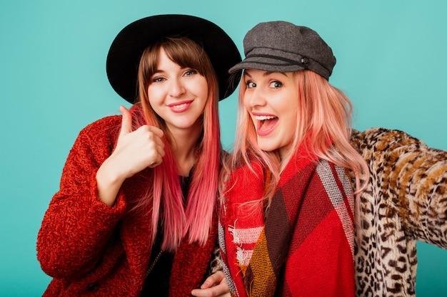 Deux belles femmes en manteaux de fausse fourrure élégants et écharpe en laine posant sur un mur turquoise