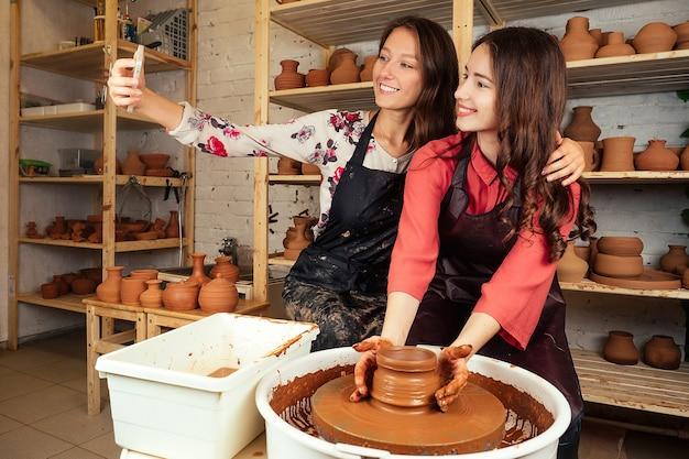 Deux belles femmes potières faisant selfie au téléphone. petite amie travaille avec de l'argile sur un tour de potier et se prend en photo dans un atelier de poterie. amusement, créativité et argile