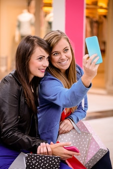 Deux belles femmes prenant un selfie dans un centre commercial