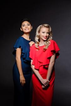 Deux belles femmes en robes de soirée souriant