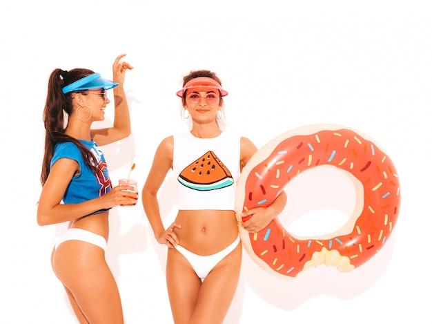 Deux belles femmes sexy souriantes en sous-vêtements d'été blancs et sujet. filles en lunettes de soleil, casquette visière transparente. modèles buvant une boisson fraîche de cocktail avec un matelas gonflable donut lilo