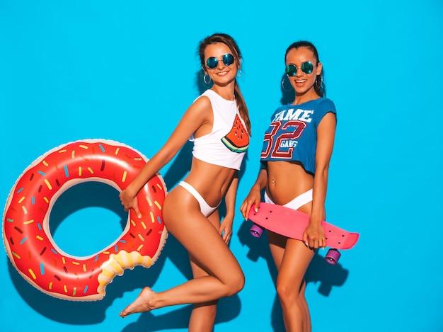 Deux belles femmes sexy souriantes en sous-vêtements d'été et sujet. filles à lunettes de soleil. des modèles positifs s'amusent avec des planches à roulettes colorées. avec matelas gonflable donut lilo