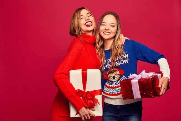 Deux belles femmes souriantes dans des pulls élégants avec de grandes coffrets cadeaux