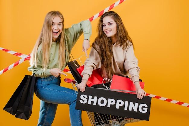 Deux belles femmes souriantes ont panier et signe de shopping avec des sacs colorés et bande de signalisation isolé sur jaune