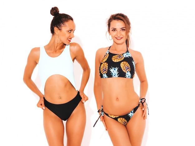 Deux belles femmes souriantes sexy en lingerie de natation. modèles chauds à la mode s'amusant. filles isolées
