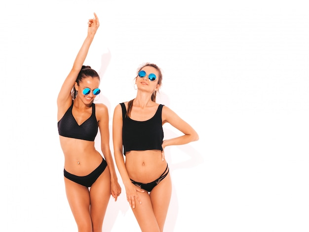 Deux belles femmes souriantes sexy en lingerie noire. modèles chauds à la mode s'amusant. filles isolées en lunettes de soleil