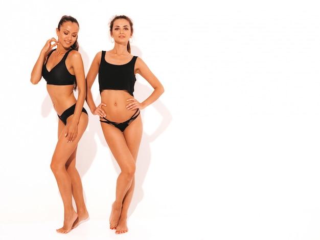 Deux belles femmes souriantes sexy en lingerie noire. modèles chauds à la mode s'amusant. filles isolées. toute la longueur