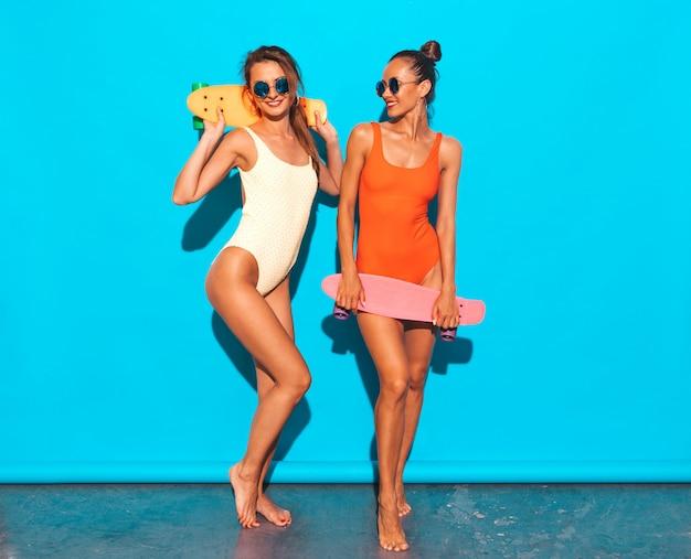 Deux belles femmes souriantes sexy en maillot de bain coloré d'été maillots de bain. filles à la mode dans des lunettes de soleil. des modèles positifs s'amusent avec des planches à roulettes colorées. isolé