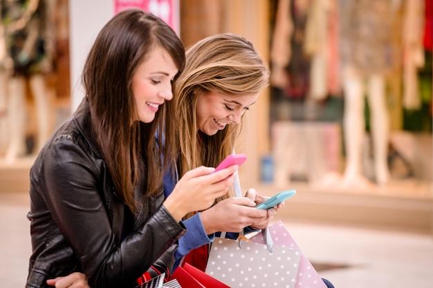 Deux belles femmes utilisant leur téléphone dans un centre commercial