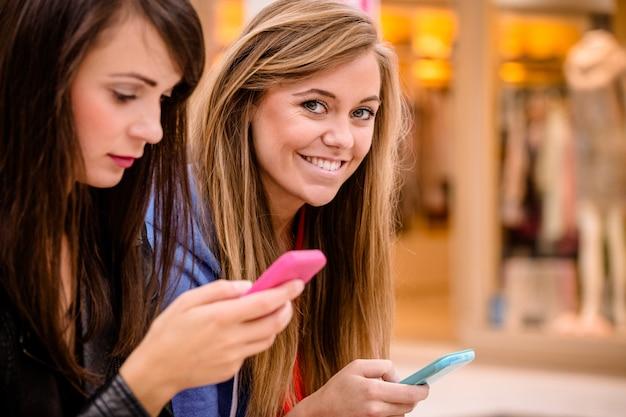 Deux belles femmes utilisant leur téléphone
