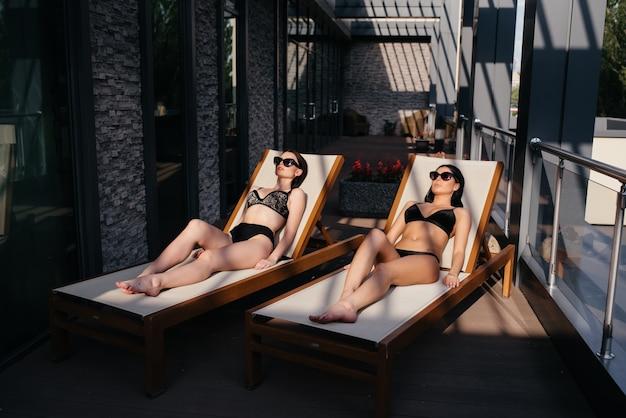 Deux belles filles allongées sur les chaises longues et se détendre.