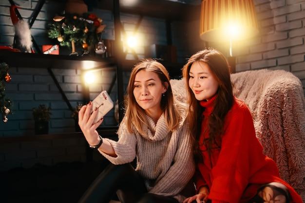 Deux belles filles asiatiques en chandails prennent un selfie sur leurs décorations de noël de téléphone portable et br ...