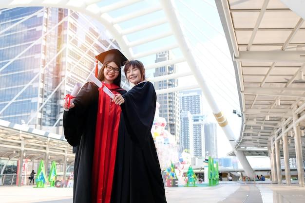 Deux belles filles asiatiques embrassent la cérémonie de remise des diplômes