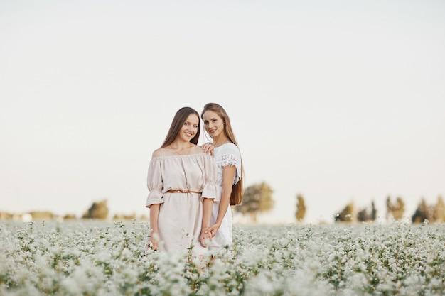 Deux belles filles aux cheveux longs dans un champ fleuri au coucher du soleil. deux belles soeurs dans un champ en fleurs