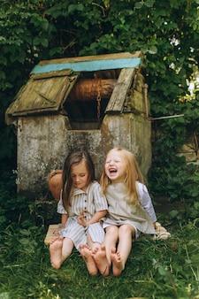 Deux belles filles en chemises antiques blanches près d'un puits sur un fond d'herbe et d'arbres