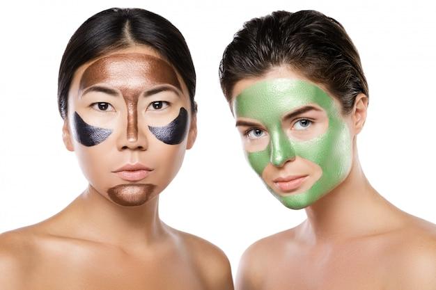 Deux belles filles avec des masques peel-off colorés sur leurs visages