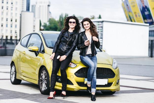 Deux belles filles modernes se tiennent près de la voiture et s'amusent