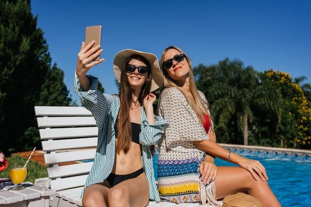 Deux belles filles prenant un selfie à côté d'une piscine