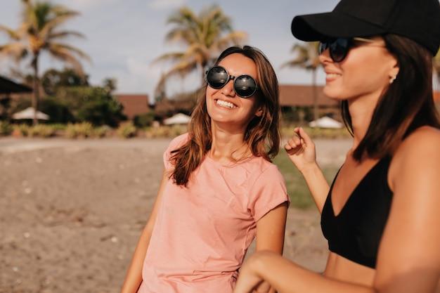 Deux belles filles de race blanche en lunettes de soleil noires marchant sur la plage de sable