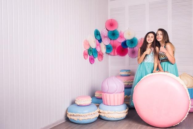 Deux belles filles en robes bleues tiennent dans leurs mains un énorme macaron en studio avec un décor de macarons. copiez l'espace.