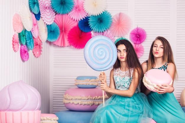 Deux belles filles en robes bleues tiennent dans leurs mains d'énormes bonbons et macarons avec décor de macarons