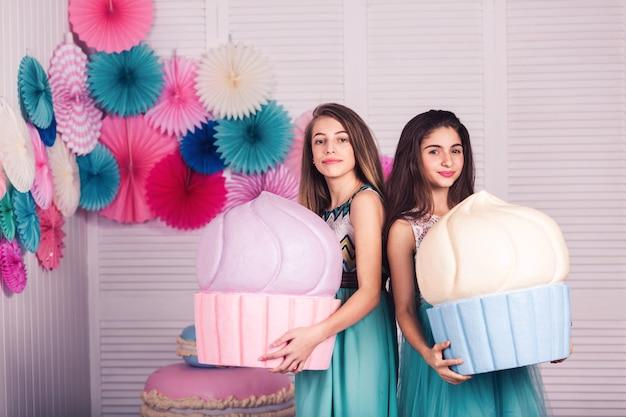 Deux belles filles en robes bleues tiennent dans leurs mains d'énormes gâteaux avec un décor de macarons